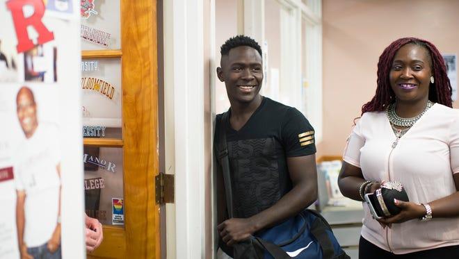 Gemel Tutu, 19, left, smiles alongside his mother Eliza Twegby Friday, June 15, 2018 at Vineland High School in Vineland, N.J.