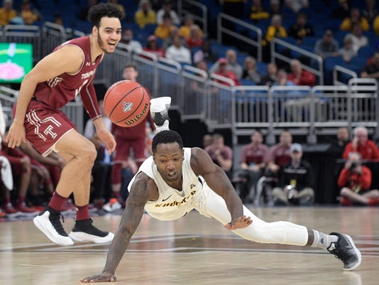 Wichita State forward Zach Brown falls to the floor after being fouled by Temple forward Obi Enechionyia (0) on a breakaway play during the second half of an NCAA college basketball game in the quarterfinals of the American Athletic Conference tournament, Friday, March 9, 2018, in Orlando, Fla. Wichita State won 89-81. (AP Photo/Phelan M. Ebenhack)