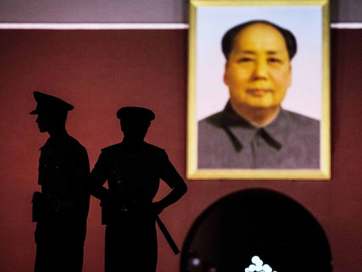Paramilitary security force officers stand under a portrait of the late Chinese leader Mao Zedong outside the Forbidden City on June 2 at Tiananmen Square in Beijing. Twenty-five years ago on June 4, 1989, Chinese troops staged a brutal crackdown on pro-democracy protesters after the government ordered the square cleared.