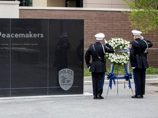 MPD officers Zach Ferrell and Sean Martin salute after placing a wreath at the Fallen Officers Wall at the Murfreesboro Police Dept. Memorial Service held at the new headquarters on Highland Ave.
