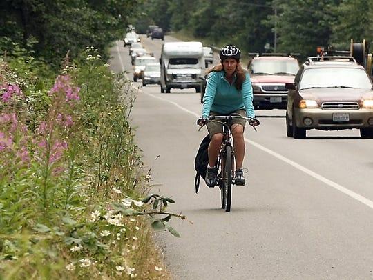 A cyclist rides on Highway 305 south of Morgan Road.  (MEEGAN M. REID / KITSAP SUN FILE)