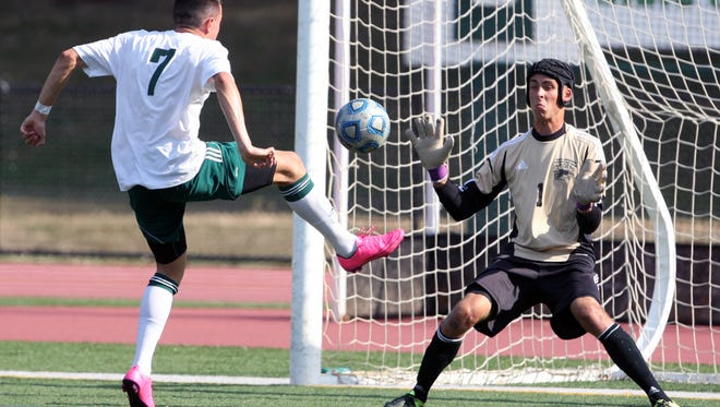 North Brunswick traveled up RT 1 to take on East Brunswick in a boys varsity soccer game in East Brunswick on Tuesday September 8,2015. North Brunswick goalie (right) Pawel Dzielski gets ready to stop the shot on goal by East Brunswick's # 7 (left)- Robert Ciuaru during the 1st half of play.
