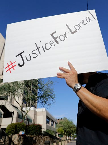Luke Black protests outside Maricopa County Attorney Bill Montgomery's office, Monday, July 25, 2016, in Phoenix. No charges will be filed against Winslow, Ariz., Police Officer Austin Shipley in the shooting death of a woman several months ago, authorities announced Friday. (AP Photo/Matt York)