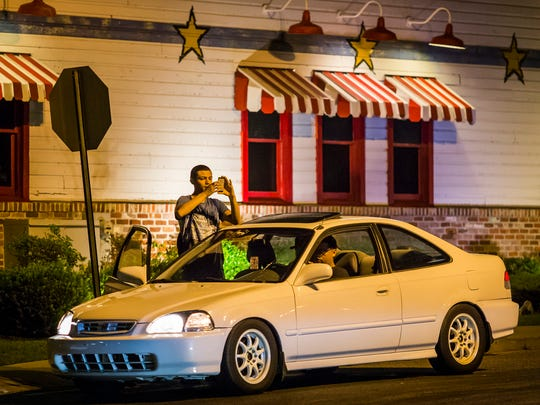 Michael Bedolla hops out of a friend's car to catch a Pokemon after the group came up from Delaware City to play Pokemon Go in the Riverfront in Wilmington on Tuesday night.