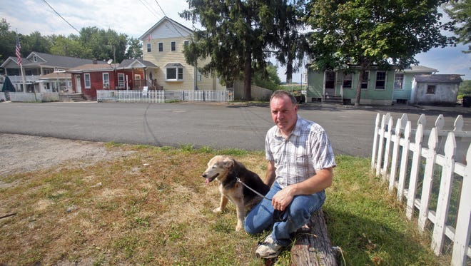 John Taggart, sits with his 16-year old dog Maggie across from his home on Warren Ave. in Haverstraw July 26, 2015. Taggart is in the process of selling the house after his lawsuit, alleging that the owners of the house next door allowed tenants to cause trouble for the rest of the neighborhood, was thrown out by a judge. The troubles culminated in a break-in to his house and a shooting. In that incident, Taggart used a rifle to shoot the intruders and accidentally shot and injured his dog.