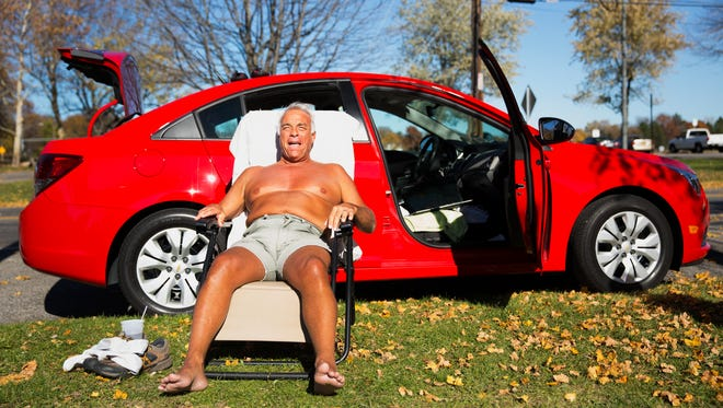 Tony Stever of Scottsville sunbathes in a lawn chair and enjoys the record-high temperature in Cobbs Hill Park on Nov. 4, 2015.