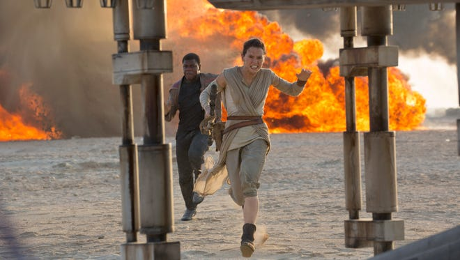 """This photo provided by Disney/Lucasfilm shows Daisy Ridley, right, as Rey, and John Boyega as Finn, in a scene from the film, """"Star Wars: The Force Awakens,"""" directed by J.J. Abrams. The movie opened Friday in U.S. theaters."""