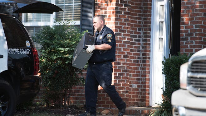 A Spartanburg County sheriff's deputy carries a computer out of the home of Todd Kohlhepp in Moore, SC on Thursday, November 3, 2016.