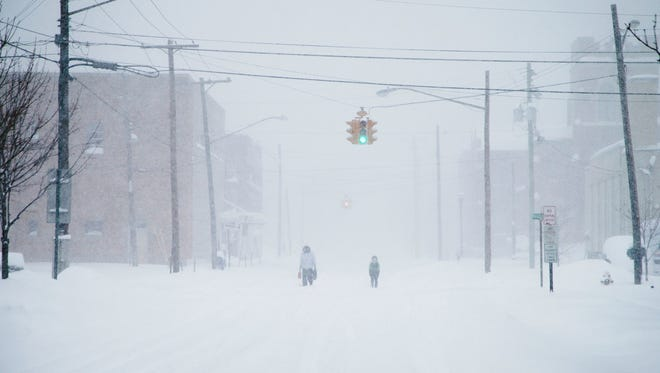 Pedestrians make their way through downtown Endicott as a huge winter storm blanketed the area with several feet of snow on March 14.