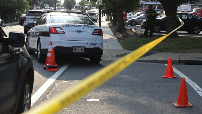 Investigators gather near the scene of a shooting in Alexandria, Va.