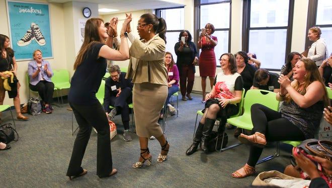 Weight Watchers member, investor and advisor Oprah Winfrey and her Weight Watchers coach celebrate with members at a Weight Watchers meeting April 19, 2016 in New York City.