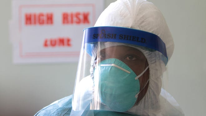 A woman wears protective clothing at one of the Ebola centers in Harare, Zimbabwe, on Sept. 23. Zimbabwe, which has not reported any cases of the deadly virus wreaking havoc in West Africa, is on high alert and has set up Ebola centers in order to screen people suspected of having the virus.