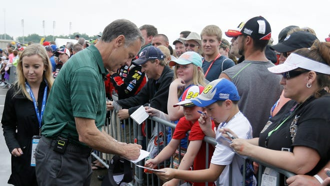 Michigan State coach Mark Dantonio signs autographs before the NASCAR race at Michigan International Speedway, Sunday in Brooklyn, Mich.