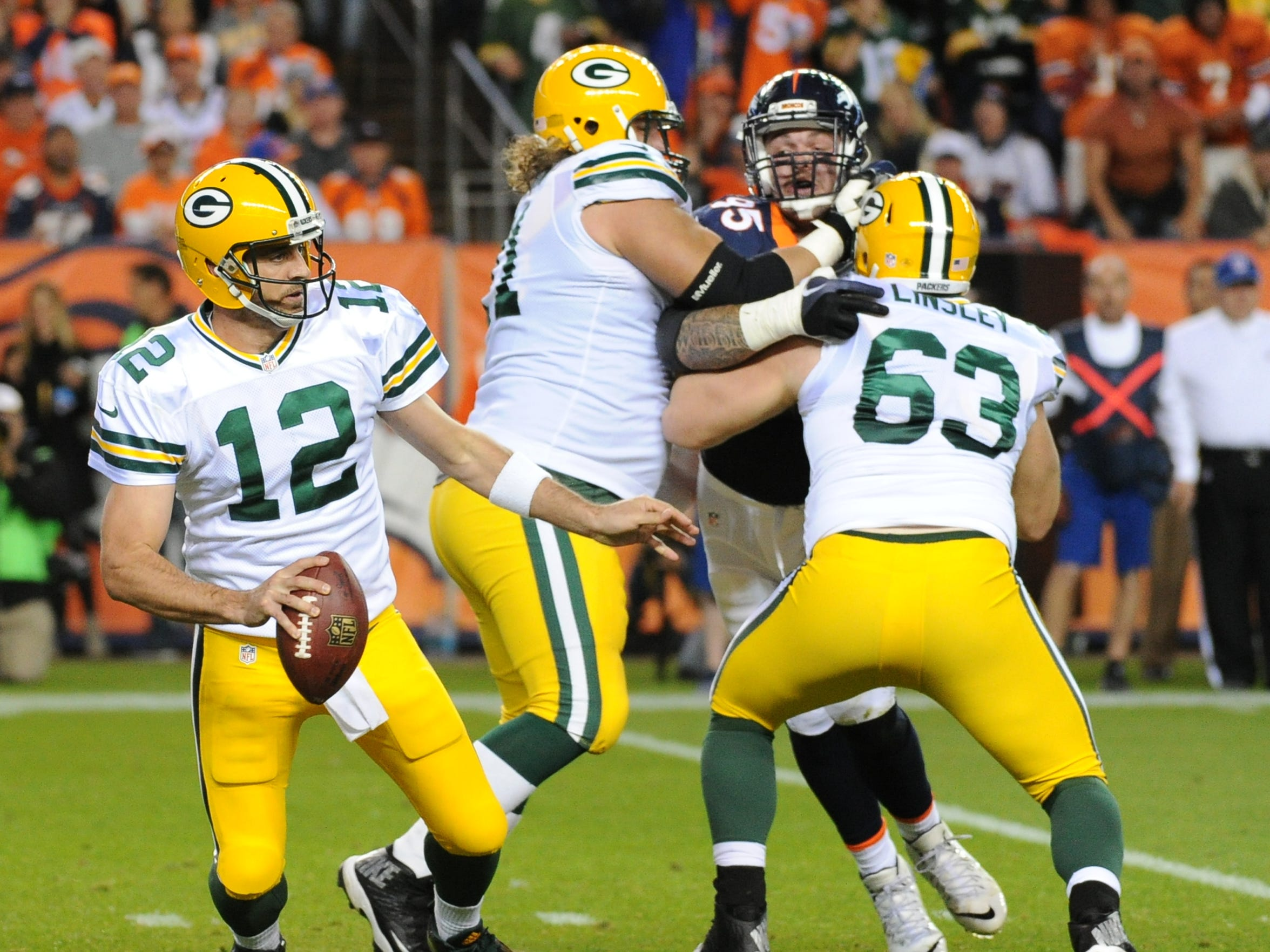 Green Bay Packers quarterback Aaron Rodgers (12) scrambles as guard Josh Sitton (71) and center Corey Linsley (63) block against the Denver Broncos at Sports Authority Field.