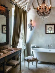 """This undated photo provided by The Monacelli Press shows detail of a bathroom in the Unicorno Garden Suite at the Borgo Santo Pietro hotel in Tuscany, Italy. Accessories specifically designed for a bathroom tend to be cold and clinical. But in this charming Italian hotel, romantic and elegant accessories like art, curtains, and lighting add warmth to the space. The photo is featured in the book """"Hotel Chic at Home"""" by Sara Bliss."""