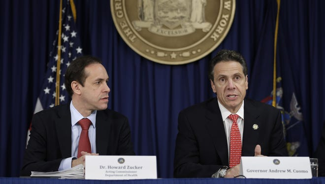 In this 2014 file photo, New York Gov. Andrew Cuomo, right, talks with Health Commissioner Howard Zucker in New York City.