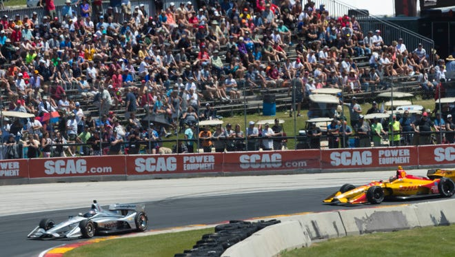 Josef Newgarden leads Ryan Hunter-Reay through Road America's Turn 5 in front of a sun-splashed crowd on his way to victory in the Kohler Grand Prix.