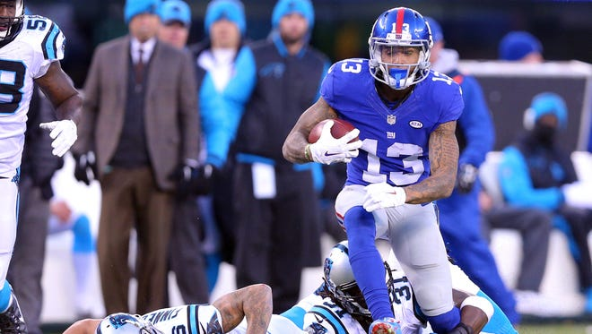 New York Giants wide receiver Odell Beckham Jr. (13) runs the ball past Carolina Panthers cornerback Cortland Finnegan (26) and defensive back Charles Tillman (31) during the fourth quarter at MetLife Stadium.