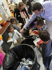 Ashley Welde of We Future Cycle and Assistant Principal James Graziano direct students to the proper recycling containers in the cafeteria at Ridgeway Elementary School in White Plains.
