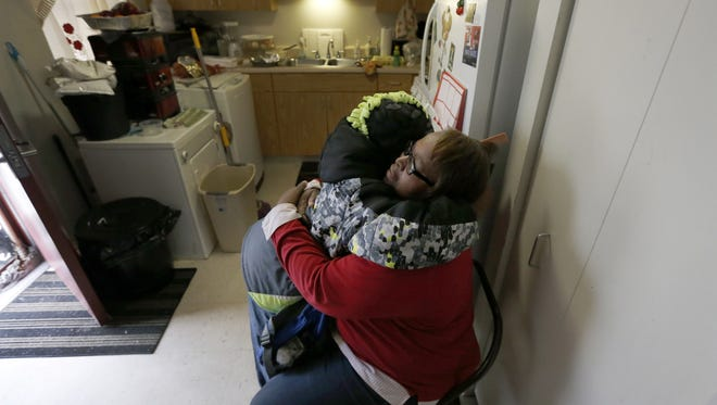 In this Jan. 29, 2016, photo, Debra Aldridge, right hugs and recites a prayer with her grandson Mario Hendricks, before the boy departed for a sleep-over at a cousin's home, at her home on Chicago's South Side. Nationwide, there are 2.7 million grandparents raising grandchildren. About a fifth have incomes that fall below the poverty line, according the Census figures. More grandparents are taking on the role of parents for their grandkids, as social service agencies try to place foster children in so-called kinship families.