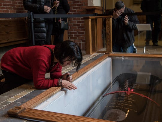 Maria Soledad Arbulu of Detroit, left, prays at Father Solanus Casey's tomb inside of the Solanus Casey Center, Friday, November 16, 2017. On the right, Khalid Majeed of Farmington prays for his family.