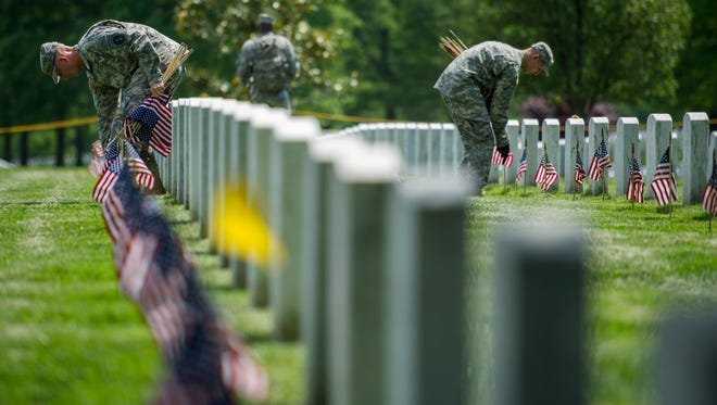 """Soldiers of the 3rd U.S. Infantry Regiment, also known as The Old Guard, places flags at grave sites at Arlington National Cemetery in Arlington, Va., Thursday, May 22, 2014, as part of the annual """"Flags-In"""" ceremony in preparation for Memorial Day. (AP Photo/Cliff Owen)"""