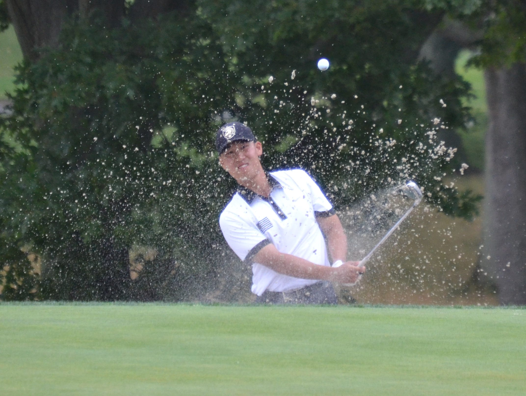Peter Kim blasts from the bunker alongside the 18th green Tuesday in a playoff to determine the Ike champion.