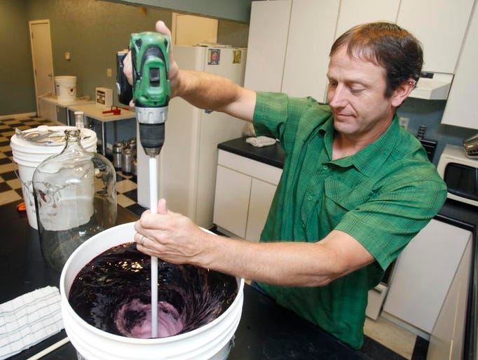 Todd Frye, owner of The Home Brewery in Ozark, mixes juice with ingredients as he demonstrates how to make wine.