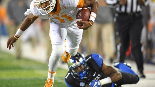 Tennessee quarterback Joshua Dobbs (11) beats a tackle by Kentucky safety A.J. Stamps (1) to score a touchdown, tying the score 7-7 during the first half at Commonwealth Stadium in Lexington, Ky. on Saturday, Oct. 31, 2015. (ADAM LAU/NEWS SENTINEL)