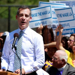 Los Angeles Mayor Eric Garcetti proposes an increase in the minimum wage for workers in the city during a Labor Day event at Martin Luther King, Jr. Park in South Los Angeles.