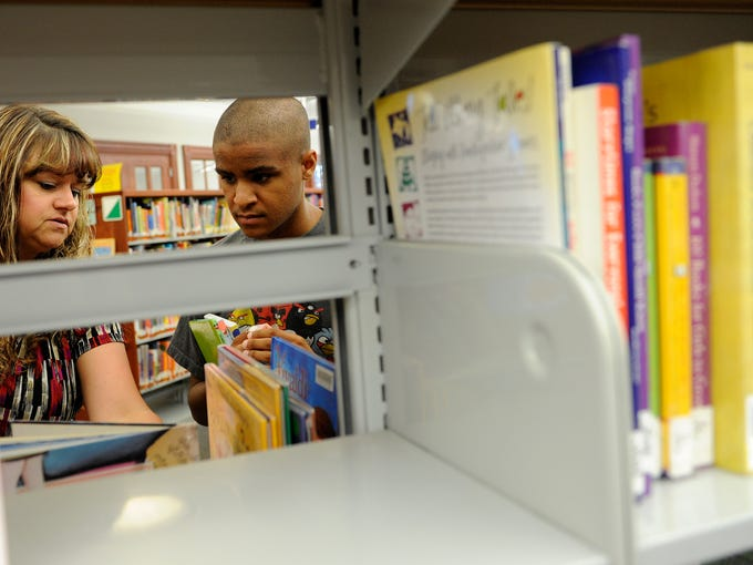 Loretta Naylor and Mac Croom look through shelves in