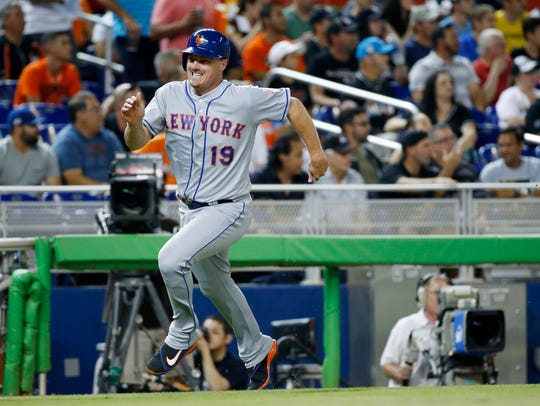 New York Mets' Jay Bruce heads home to score on a single