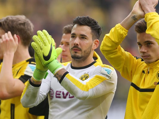 FILE - In this April 15, 2017 photo Dortmund's goalkeeper Roman Buerki und Raphael Guerreiro, right, cheer towards their fans after the German Bundesliga soccer match between Borussia Dortmund and Eintracht Frankfurt in Dortmund, Germany. Borussia Dortmund goalkeeper Roman Buerki says he's still having trouble sleeping after the attack on his team's bus on April 11, and says he couldn't concentrate properly in the delayed Champions League match a day later.  (Ina Fassbender/dpa via AP,file)