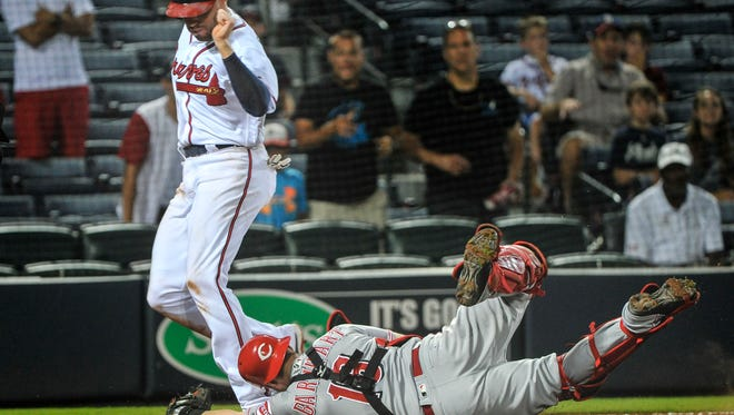 The Atlanta Braves' Freddie Freeman is forced out at home plate by Cincinnati Reds catcher Tucker Barnhart (16) on a grounder by Jace Peterson which Barnhart fielded during the 11th inning of a baseball game, Wednesday, June 15, 2016, in Atlanta.