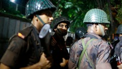 Bangladeshi security personnel stand guard near a restaurant