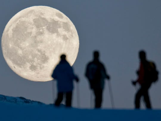 Three snow hikers watch the almost-full moon rise in