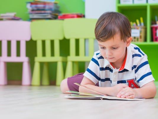 boy kid lay down on floor and reading tale book in preschool library,Kindergarten school education concept