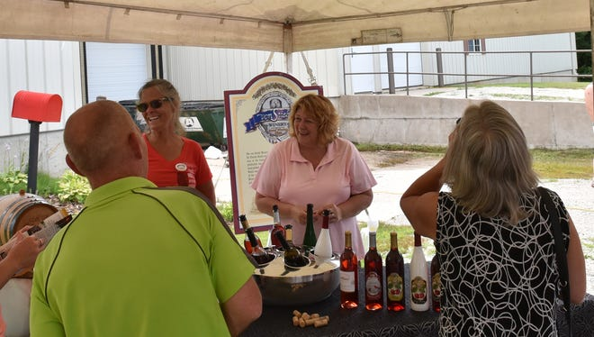 Patti Raine, left, and Sallie Marquardt, right, offer wine samples from von Stiehl Winery of Algoma.