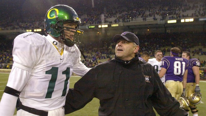 Former Washington coach Keith Gilbertson, right, talks with former Oregon quarterback Kellen Clemens following their game Saturday, Nov. 1, 2003, in Seattle. Washington won 42-10. It was the last time that the Huskies beat the Ducks. (AP Photo)