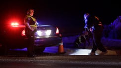 Officials investigate near the area of an explosion,