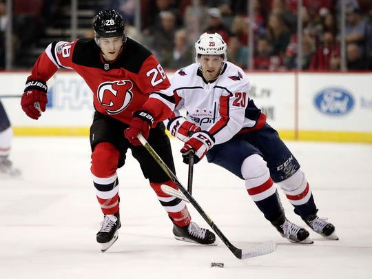 New Jersey Devils defenseman Damon Severson (28) competes for the puck with Washington Capitals center Lars Eller (20), of Denmark, during the first period of an NHL hockey game, Friday, Oct. 13, 2017, in Newark, N.J. (AP Photo/Julio Cortez)