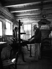 Harry Oliver at his printing press setting type.