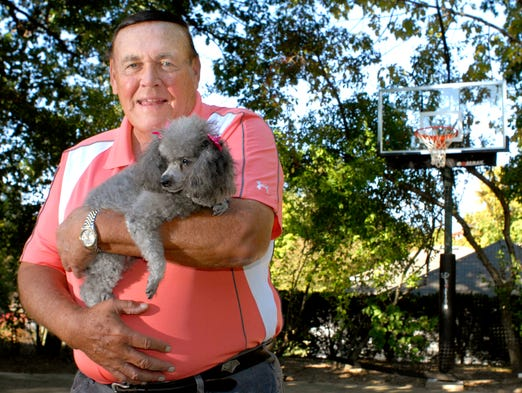 Former Purdue basketball coach Gene Keady holds his miniature poodle, Queen, at his home in Lafayette on October 1, 2010.