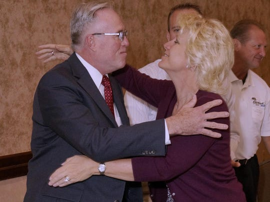 Jim Demmer gets a hug from Linda Demmer, his spouse.