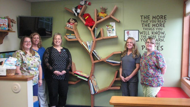 """Community Pediatrics support staff members are shown near the Reading Tree in the waiting room of the Beaver Dam Clinic.  Children are encouraged to take home a """"gently used"""" book and share it with other family members.  Pictured left to right are: Katelyn Aumann, medical assistant; Cinnamon Mayoh, registered nurse; Sheila Schumann, administrative assistant; Gina Roberts, LPN; Tina Smedema, certified medical assistant."""