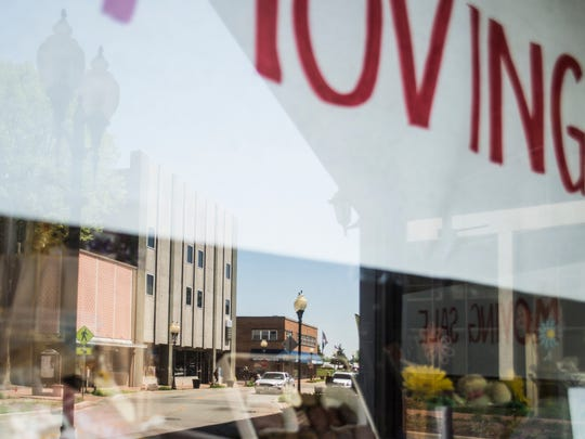 Businesses in the 600 block of East Main Street are reflected in a window of Olympian Candies on Monday, May 7, 2018.