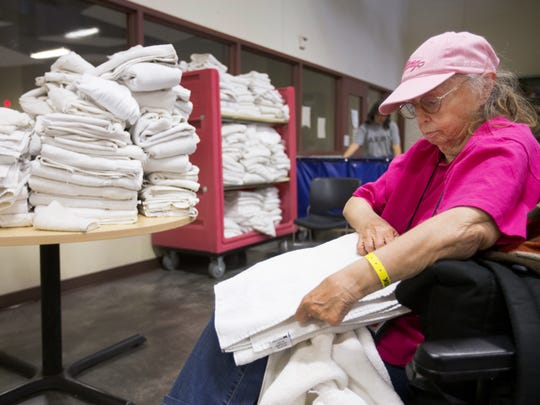 Mary Ann Rentmeister folds towels at Central Arizona Shelter Services as part of her chores.