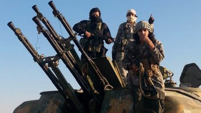 Fighters from the Islamic State sit atop a military vehicle in Raqqa, Syria, in August.
