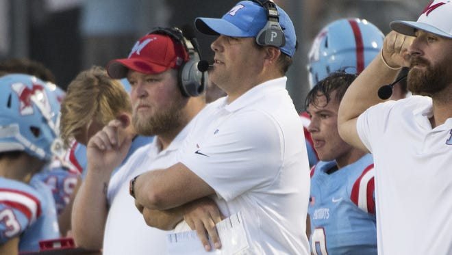 After 12 years as an assistant, Kevin Burnette, center, is in his first season as a head football coach, leading the program at J.L. Mann.