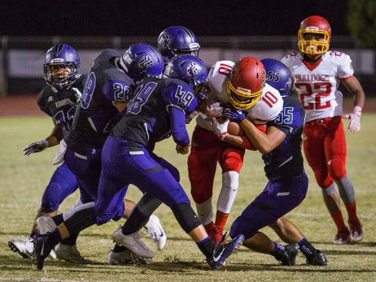 Kyle Serna (#10) was met by four Shadow Hills defenders but managed to get the Bulldogs a first down.